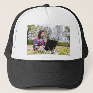 Woman sits with laptop in blooming meadow trucker hat