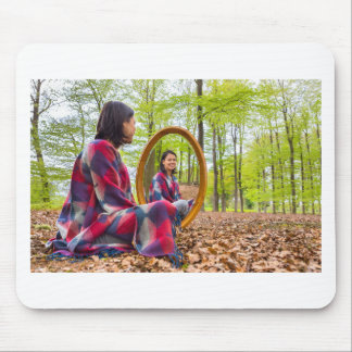 Woman sits with mirror in forest during spring mouse pad