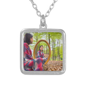 Woman sits with mirror in forest during spring silver plated necklace