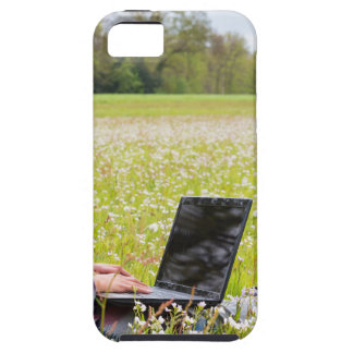 Woman sitting with laptop in spring meadow case for the iPhone 5