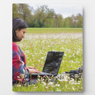 Woman sitting with laptop in spring meadow plaque