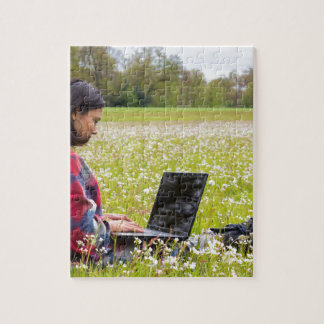 Woman sitting with laptop in spring meadow puzzles