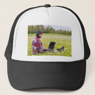 Woman sitting with laptop in spring meadow trucker hat