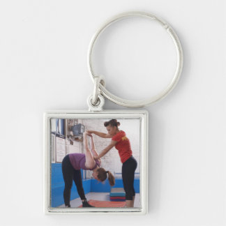 Woman stretching with trainer in gym key chains