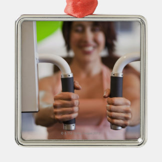 Woman using exercise machine in gym metal ornament