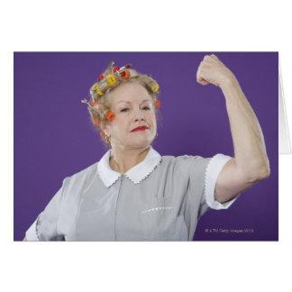 Woman wearing hair curlers, tensing arm muscles, card