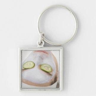 Woman with face mask and cucumber slices on key ring