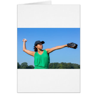 Woman with glove and cap throwing baseball outside card