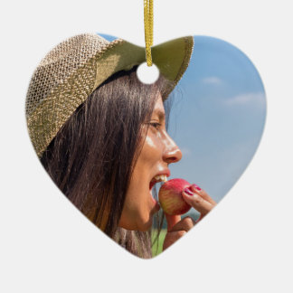 Woman with hat eating red apple outside ceramic heart decoration