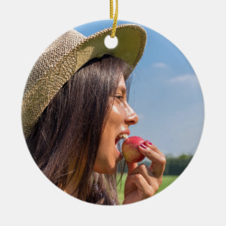 Woman with hat eating red apple outside round ceramic decoration