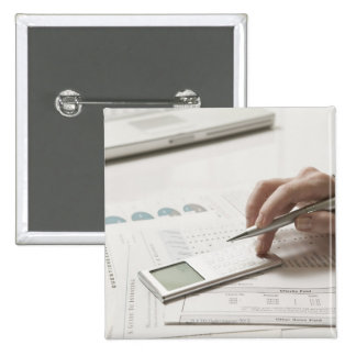 Woman working on financial paperwork and 15 cm square badge