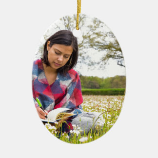 Woman writing in meadow with spring flowers ceramic oval decoration