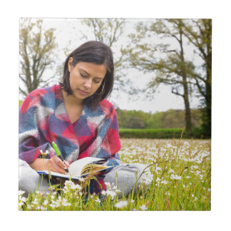 Woman writing in meadow with spring flowers ceramic tile