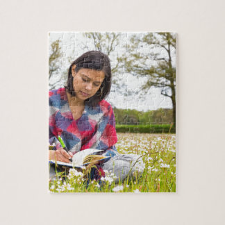Woman writing in meadow with spring flowers jigsaw puzzle