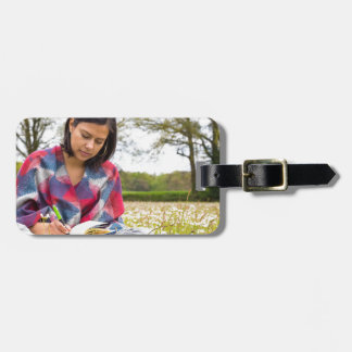 Woman writing in meadow with spring flowers luggage tag