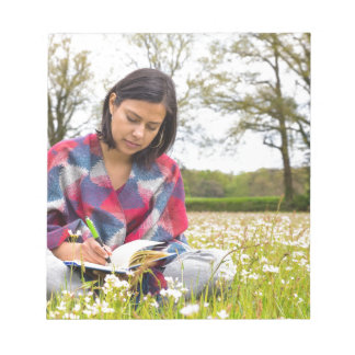 Woman writing in meadow with spring flowers notepad