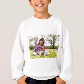 Woman writing in meadow with spring flowers sweatshirt
