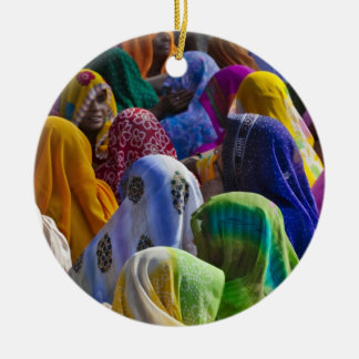 Women in colorful saris gather together round ceramic decoration
