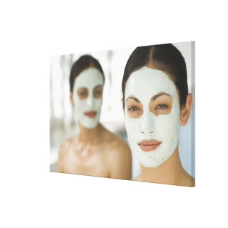 Women smiling in beauty mud masks stretched canvas prints