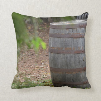 wooden barrel right with green frond left cushion