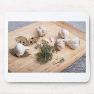 Wooden board with garlic and dried spices closeup mouse pad