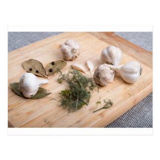 Wooden board with garlic and dried spices closeup postcard
