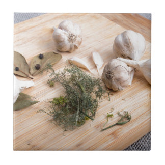 Wooden board with garlic and dried spices closeup small square tile
