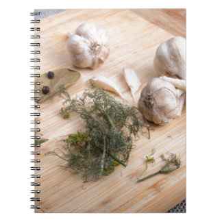 Wooden board with garlic and dried spices closeup spiral note book