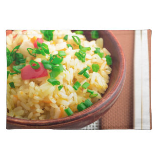 Wooden bowl of cooked rice and vegetables placemat
