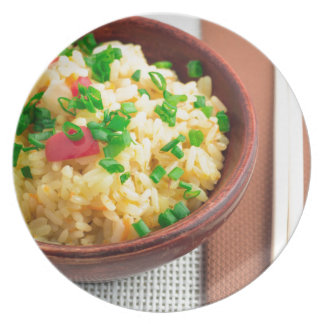 Wooden bowl of cooked rice and vegetables plate