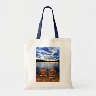 Wooden chairs at sunset on lake shore budget tote bag