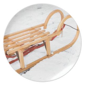 Wooden children sled in winter snow plate
