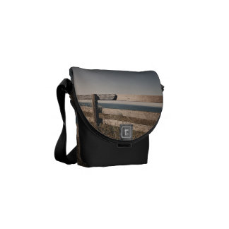 Wooden fence by the sea messenger bags