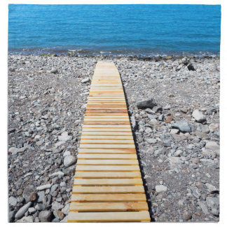 Wooden footpath on beach leading to portuguese sea napkin