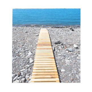 Wooden footpath on beach leading to portuguese sea notepad