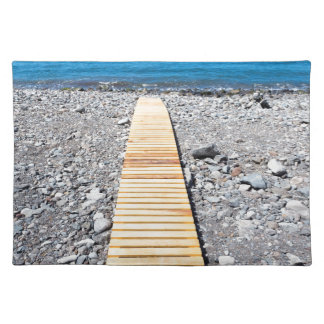 Wooden footpath on beach leading to portuguese sea placemat