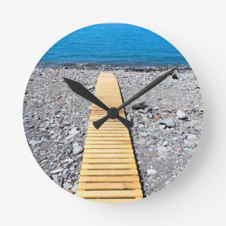 Wooden footpath on beach leading to portuguese sea round clock