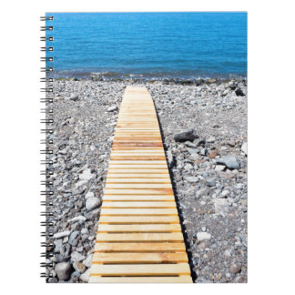 Wooden footpath on beach leading to portuguese sea spiral notebook