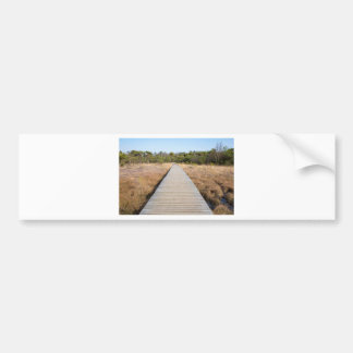 Wooden path in grass and forest winters landscape. bumper sticker