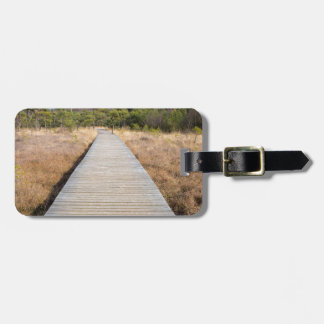 Wooden path in grass and forest winters landscape. luggage tag