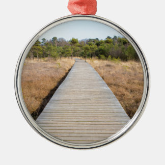 Wooden path in grass and forest winters landscape. Silver-Colored round decoration