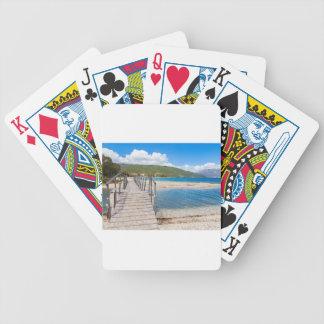 Wooden pedestrian bridge on greek beach bicycle playing cards