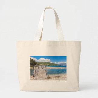 Wooden pedestrian bridge on greek beach large tote bag