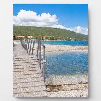 Wooden pedestrian bridge on greek beach plaque