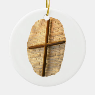 Wooden thin cross on white brick church wall round ceramic decoration