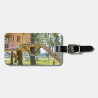 Wooden tree house in oak tree with grass luggage tag