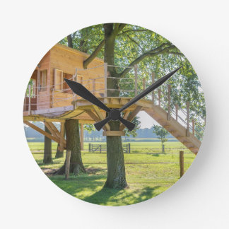 Wooden tree house in oak tree with grass round clock
