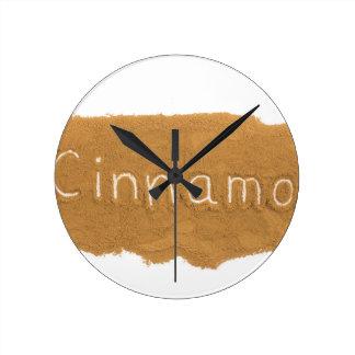 Word written in Cinnamon powder on white backgroun Round Clock