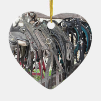 Worn leather horse bridles hanging on wooden fence ceramic ornament