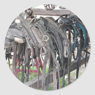 Worn leather horse bridles hanging on wooden fence classic round sticker